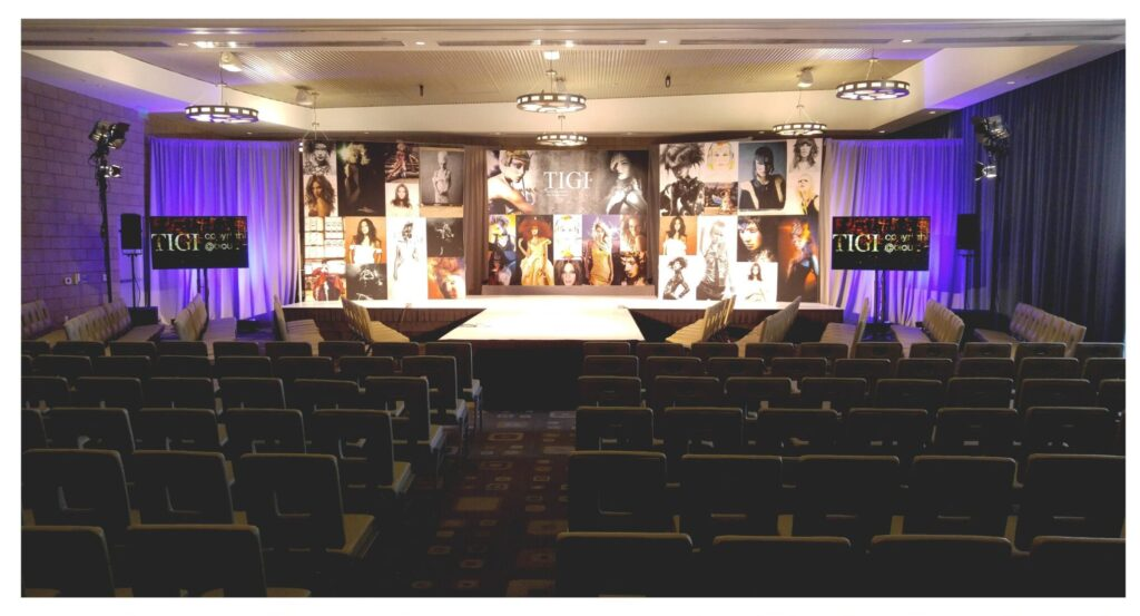 stage uplighting with large stage pieces and well-lit room with television for audience to see messaging